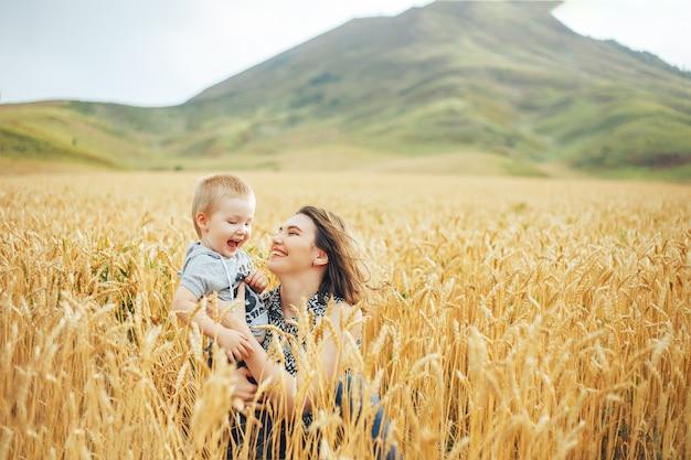 若くて美しい女性が小麦の牧草地で彼女の幼児の赤ちゃんと遊ぶこと。 Premium写真