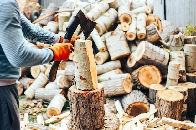 ジーンズと市松模様のシャツの手で斧で切り株の近くに立っている男 Premium写真