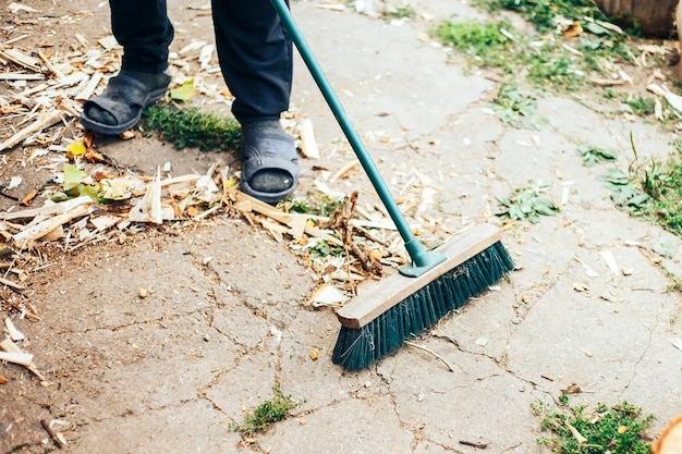作業用手袋の男性の手の中にゴミと古いほうきと金属スクープ Premium写真