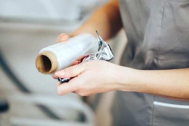女性は不妊のためのラップテープを使用するために恒久的な化粧のための器具を準備します Premium写真