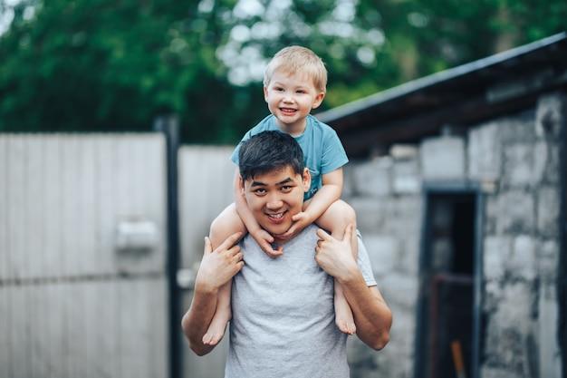 Блондинка трехлетний мальчик сидел на плечах отца. казахский папа и кавказская мама. счастливый отец с черными волосами играет со своим кавказским сыном Premium Фотографии