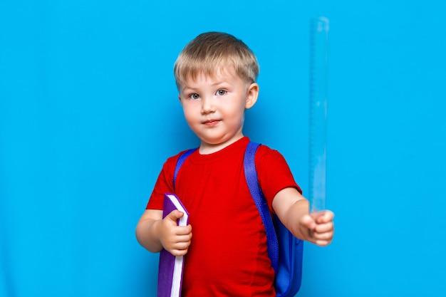 Маленький счастливый улыбающийся мальчик с очками на голове, книга в руках, плечи на плечах. обратно в школу. готов к школе Premium Фотографии