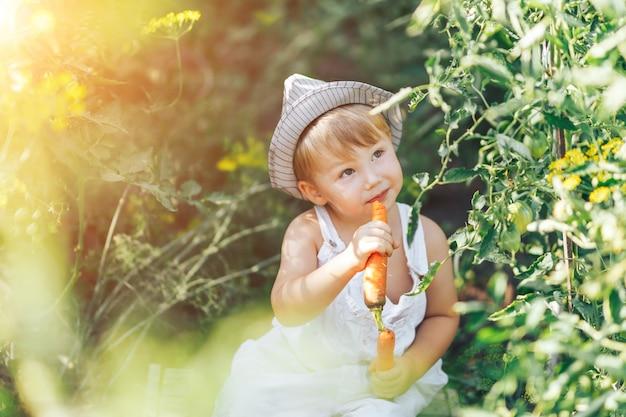 ニンジンと緑の草に座っているカジュアルな服装の赤ちゃん農家 Premium写真