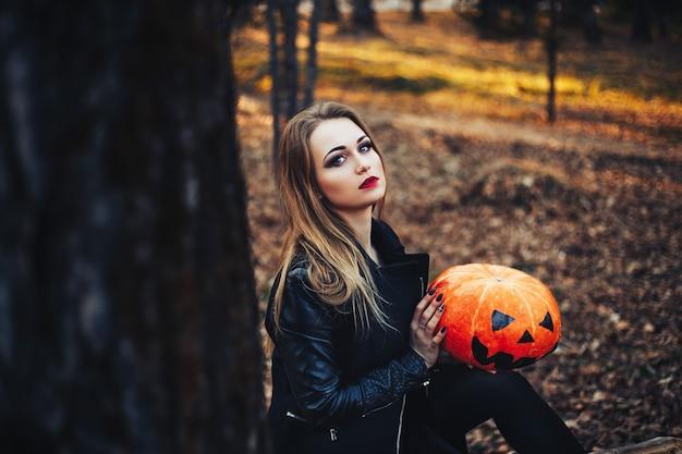 Красивая современная ведьма держа тыкву хеллоуина в лесе. октябрь. счастливых праздников Premium Фотографии