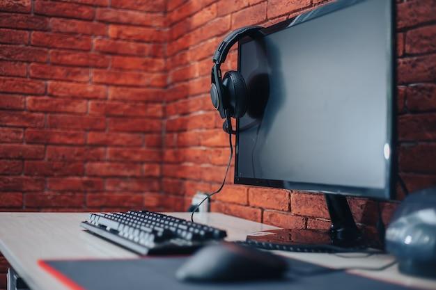 自宅のレンガの背景にテーブルの上のコンピューターのヘッドフォンキーボードマウス Premium写真
