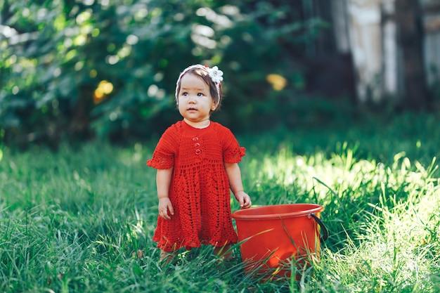 美しい咲く果樹園でピクニックを楽しんでいる赤いドレスを着てニット花の冠を持つ愛らしい幸せな幼児の女の子 Premium写真