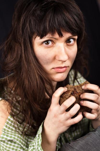 一切れのパンを持つ乞食女 Premium写真