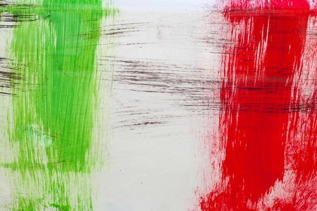 イタリアの国旗は白い背景の上のブラシストロークで描かれました。 Premium写真