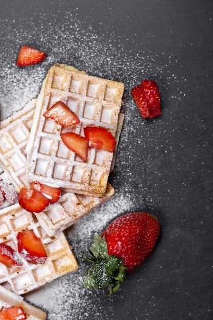Бельгия вафли с клубникой и сахарной пудрой на черной доске. Premium Фотографии