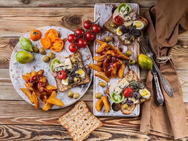アボカド、ウズラの卵、トマト、ドーブルーチーズ、フライドポテトで食欲をそそるトースト。 Premium写真