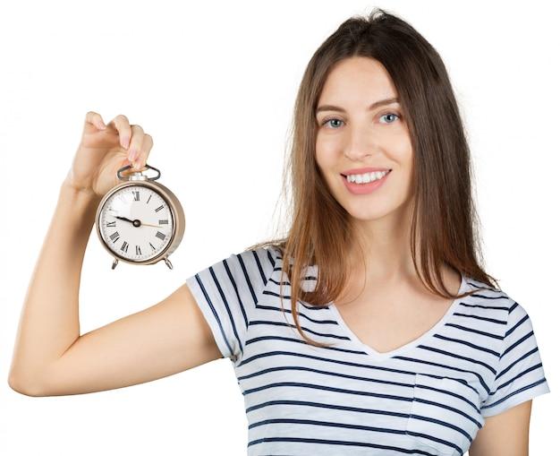 白で隔離される目覚まし時計を持つ若い女。時間管理の概念 Premium写真