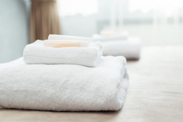 Белое полотенце на кровати в комнате для гостей отеля Premium Фотографии