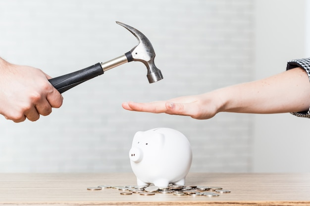 白い貯金箱の上に上げられているハンマーを持っている手 Premium写真