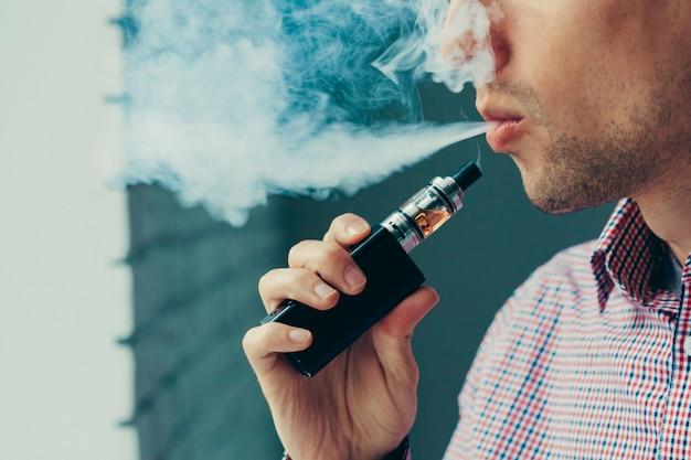 電子タバコから蒸気を吐き出す男にクローズアップ Premium写真