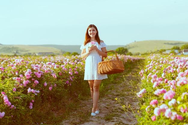 Красивая молодая женщина позирует возле розы в саду. Premium Фотографии