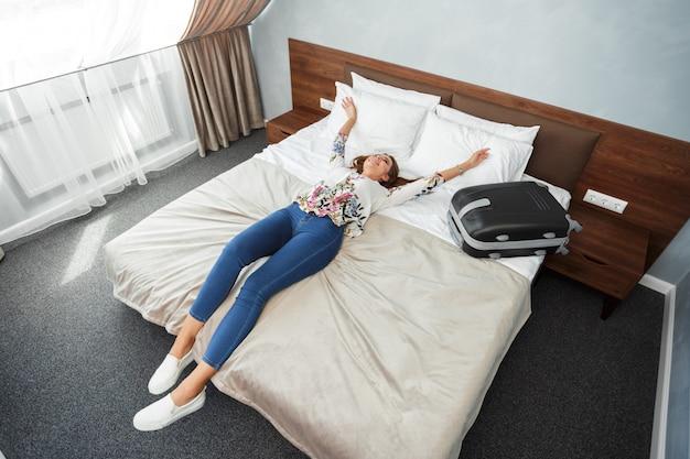 ホテルの部屋のベッドで横になっている若い女性 Premium写真