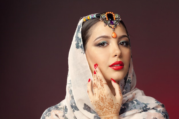 Красивая женщина в восточном стиле с мехенди на темном Premium Фотографии