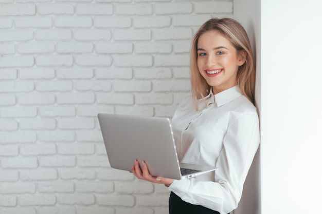 オフィスで働く美しい若い女性の肖像画。 Premium写真