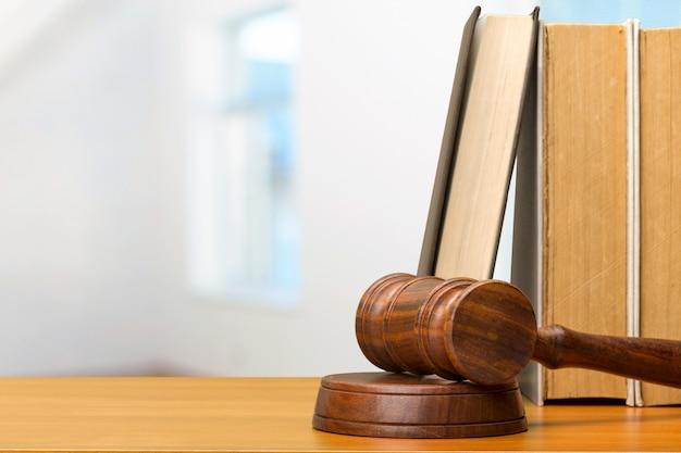 木製の小槌と木製のテーブルの上の本 Premium写真