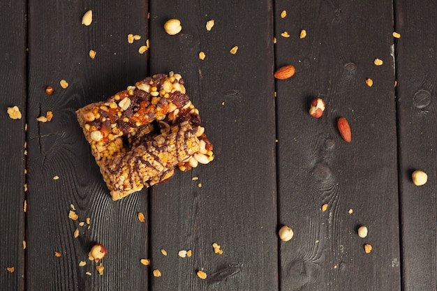 ナッツ、種子、ドライフルーツ、木製のテーブルの上の健康的なバー Premium写真