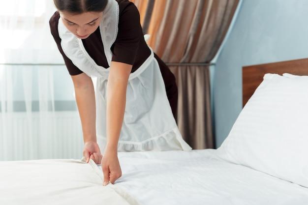 Молодая горничная делает кровать в гостиничном номере Premium Фотографии