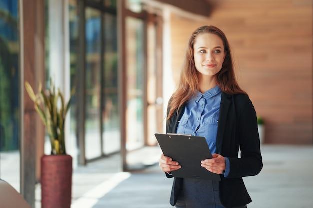 オフィスでクリップボードと幸せな美しいビジネス女性。 Premium写真