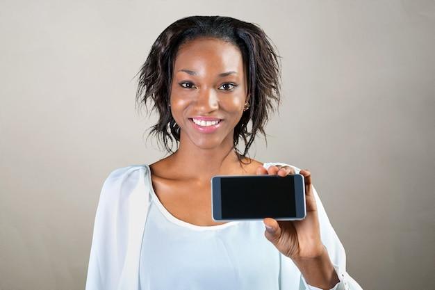 アフリカ系アメリカ人の女性が携帯電話を表示 Premium写真