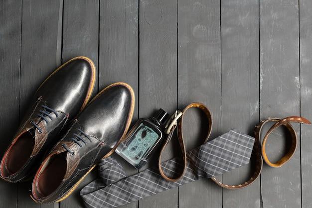 Обувь и аксессуары для мужчин лежали на деревянном полу Premium Фотографии
