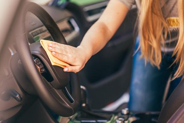 マイクロファイバーの布で車を掃除する手 Premium写真