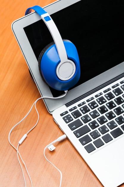テーブルの上のノートパソコンとヘッドフォンをクローズアップ Premium写真