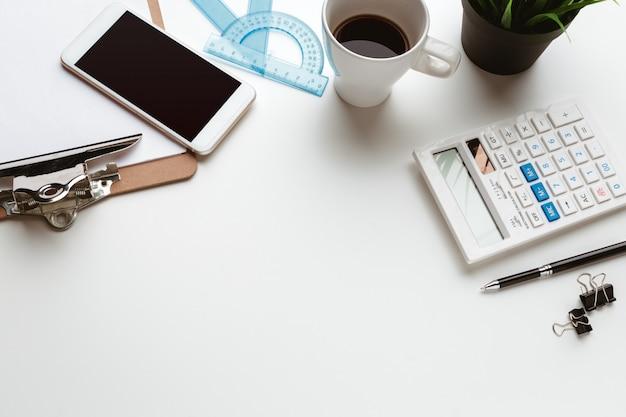 白いテーブルの上の創造的な障害にドロップされたビジネスアイテム Premium写真