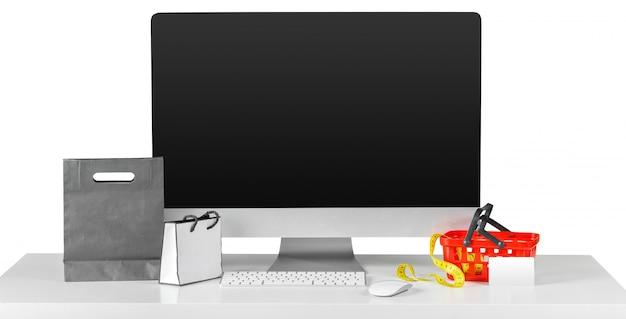 ショッピングアクセサリーとテーブルの上のコンピューターモニター画面 Premium写真