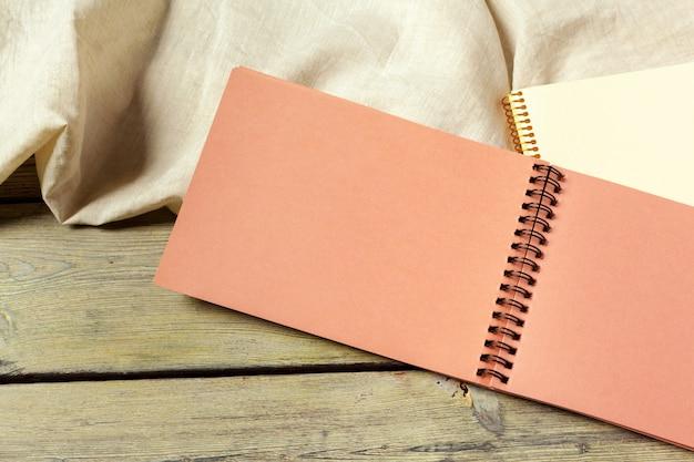 一枚の布で木製の背景の空白の開いているメモ帳 Premium写真