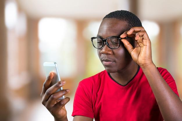 スマートフォンを使用して笑顔の若いアフリカ人の肖像画 Premium写真