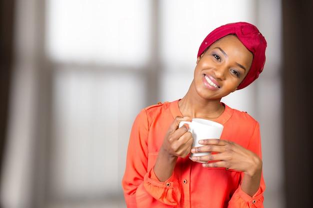 Счастливый афро-американских женщина пьет чай из чашки или кружки Premium Фотографии