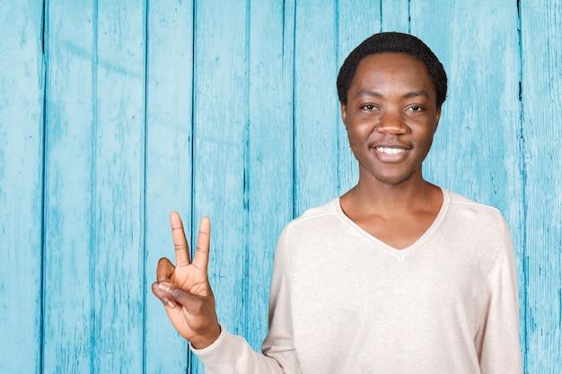 Молодой крутой черный человек знак победы Premium Фотографии