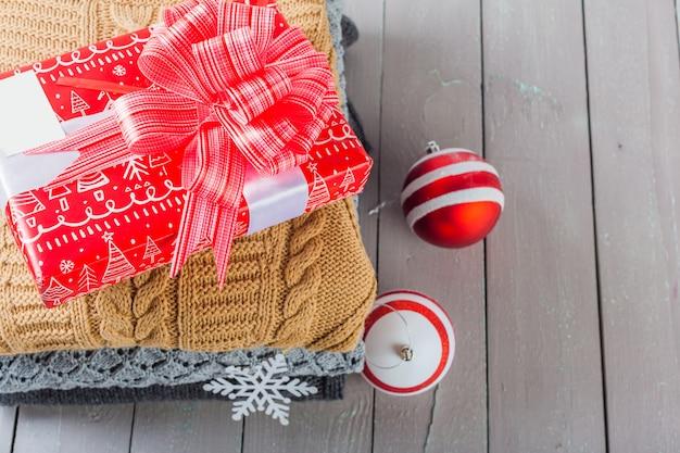 木製のテーブルの上の白い居心地の良いニットセーターのスタック Premium写真