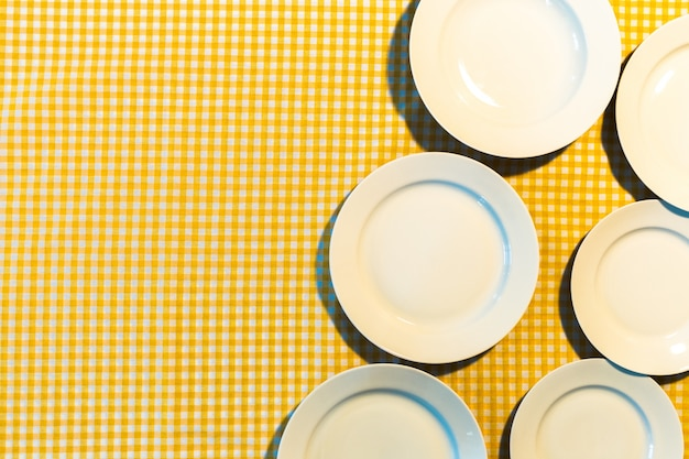 黄色の市松模様のテーブルクロスの上の皿 Premium写真