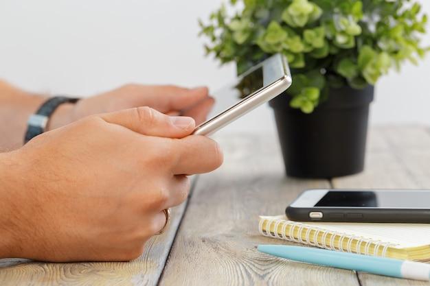木製のワークスペーステーブルの上にタブレットデバイスをかざす男の手 Premium写真