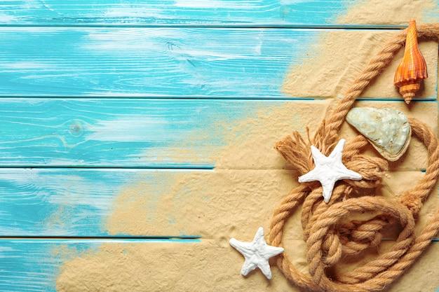 青い木製の背景に海砂の上のさまざまな貝殻を持つ海のロープ。上面図 Premium写真