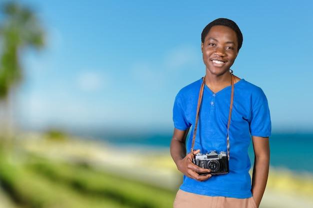 レトロなカメラで写真を作る笑みを浮かべてアフロアメリカンの男の肖像 Premium写真