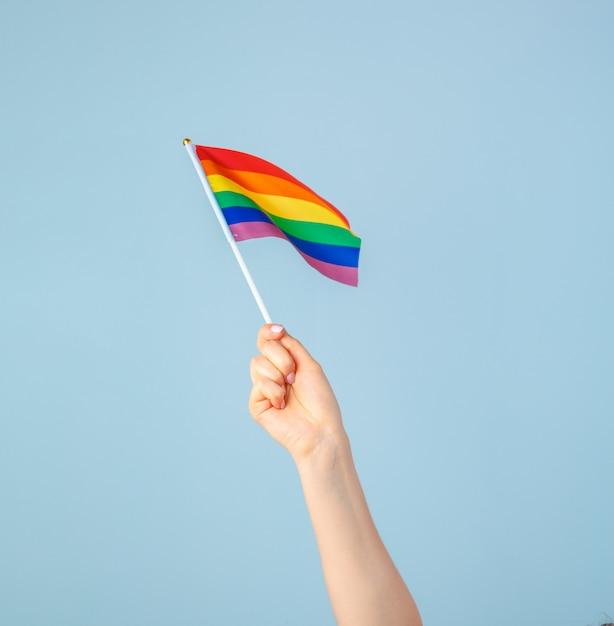 Макрофотография руки, размахивая небольшой радужный флаг против светло-голубой Premium Фотографии