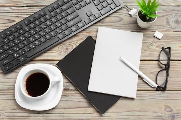 メガネと文房具と木製のデスクトップの平面図をクローズアップ。モックアップ Premium写真