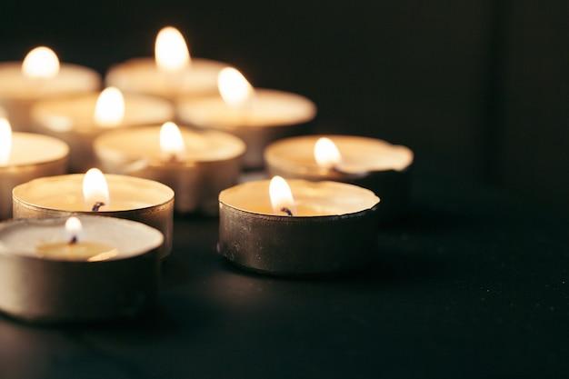 Горящая свеча на таблице в темноте, космосе для текста. похоронный символ Premium Фотографии