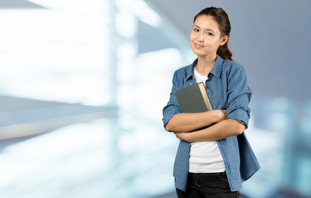 Портрет счастливый студент девушка или женщина с книгами в библиотеке Premium Фотографии