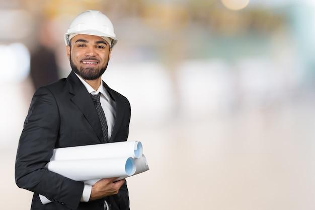 スタジオで分離された計画を保持している黒の建築家の自信を持って笑顔の肖像画 Premium写真