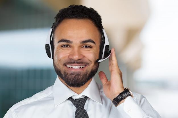 ヘッドセットが働いているとコールセンターのオペレーター男 Premium写真