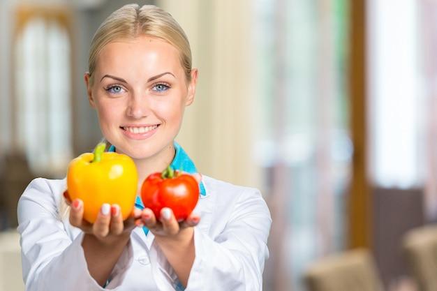 分離された新鮮な野菜を保持している白いガウンで笑顔の女性医師の肖像画 Premium写真