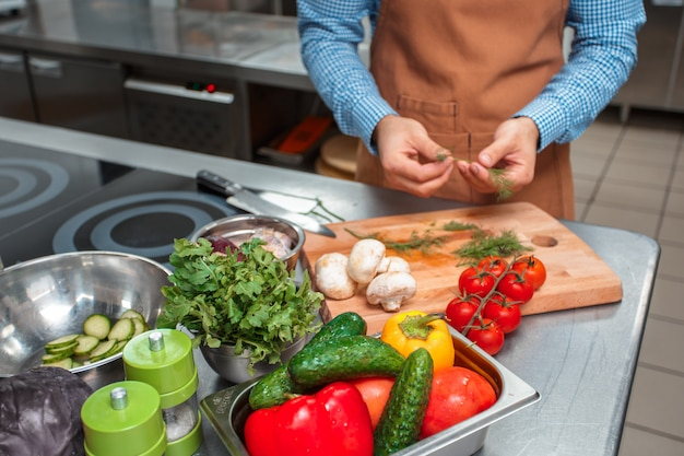 レストランのキッチンで調理する茶色のエプロンのシェフ Premium写真