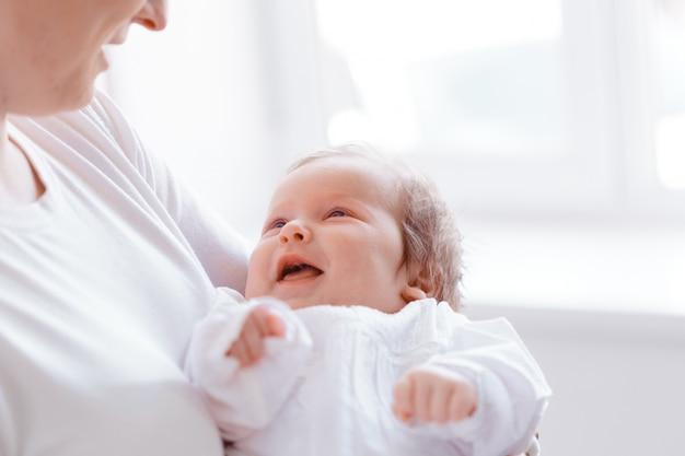 Молодая мама и новорожденный ребенок в белой спальне Premium Фотографии